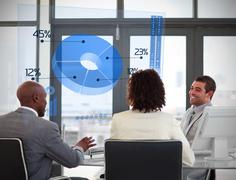 Stock Photo of Smiling business people using blue pie chart on futuristic interface