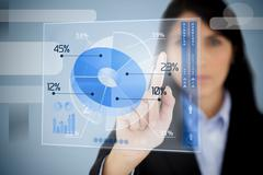 Serious businesswoman using blue pie chart interface - stock photo