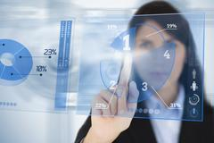 Serious businesswoman using blue pie chart futuristic interface - stock photo