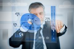 Charismatic businessman using blue pie chart interface Stock Photos