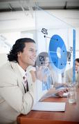 Smiling businessman looking at blue pie chart interface Stock Photos