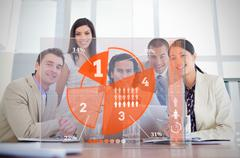 Smiling business workers looking at orange pie chart interface Stock Photos