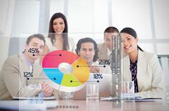 Smiling business workers looking at colorful pie chart interface - stock photo