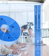 Serious business people using blue pie chart interface - stock photo