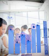 Group of colleagues using blue chart interface Stock Photos