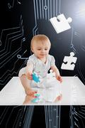 Baby holding jigsaw piece sitting on white reflective surface - stock photo