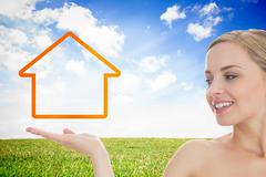Smiling woman looking at house outline - stock photo