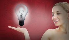 Smiling woman with light bulb inside her hand Stock Photos