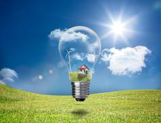 Light bulb showing house and turbines in a field Stock Photos