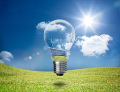 Light bulb showing solar panels and turbines in a field Stock Photos