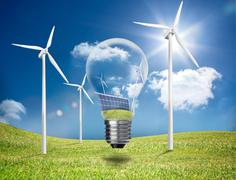 Light bulb showing solar panels and turbines in a field with wind turbines Stock Photos