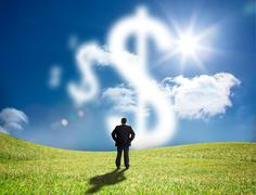 Businessman looking at cloud dollar signs - stock photo