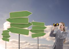 Businesswoman looking at empty signposts with binoculars Stock Photos