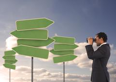 Stock Photo of Businessman looking at empty signposts with binoculars