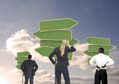 Stock Photo of Group of businesspeople looking at empty signposts