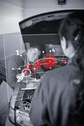 Two mechanics looking at futuristic interface - stock photo