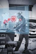 Mechanic typing while consulting futuristic interface - stock photo