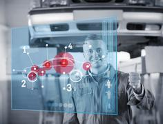Portrait of smiling mechanic thumbs up with futurist interface in black and Stock Photos