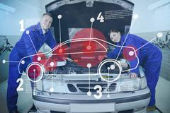 Two happy mechanics consulting futuristic interface with open hood Stock Photos