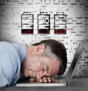 Businessman sleeping on his laptop with no battery symbols - stock photo