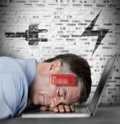 Businessman sleeping on his laptop with low energy and charging symbols Stock Photos
