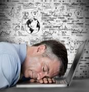 Businessman sleeping on his laptop with drawings and charts Stock Photos
