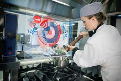 Chief preparing food while consulting futuristic interface - stock photo
