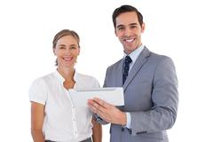 Smiling co workers using a tablet pc - stock photo