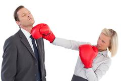 Businesswoman hitting colleague with boxing gloves - stock photo