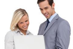 Business people looking at laptop and smiling Stock Photos