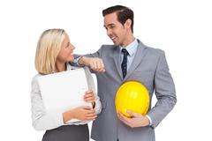 Architects with plans and hard hat smiling at each other - stock photo