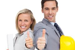 Young architects with plans and hard hat showing thumbs up - stock photo