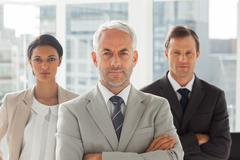 Stock Photo of Serious businessman standing with colleagues behind
