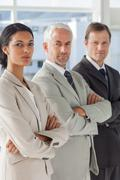 Three serious business people standing together - stock photo