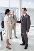 Two people shaking their hands with colleague watching them - stock photo