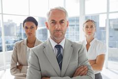 Stock Photo of Serious businessman standing in front of colleagues