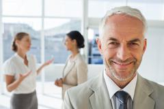 Smiling businessman standing in front of colleagues - stock photo