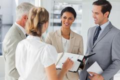 Smiling business people making an appointment - stock photo
