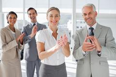 Smiling business people applauding together Stock Photos