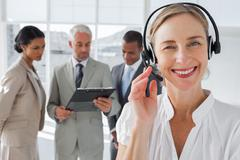 Close up of smiling woman standing with a headset - stock photo