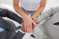 United team piling up their hands together - stock photo
