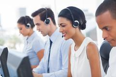Smiling call center employees sitting in line Stock Photos