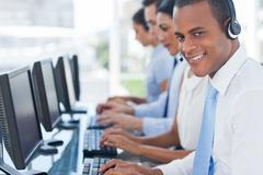 Stock Photo of Smiling agent smiling while working