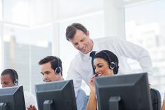 Stock Photo of Manager listening to call centre employee