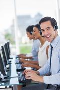 Joyful call centre agent working - stock photo