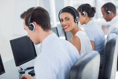 Stock Photo of Attractive call centre employee looking over shoulder