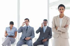 Businesswoman standing in front of business people Stock Photos