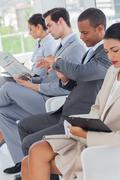 Business people sat in line Stock Photos