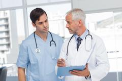 Doctors talking about a file - stock photo