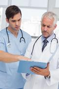 Two doctors talking about a file - stock photo